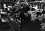 Pessoas lendo jornal no trem