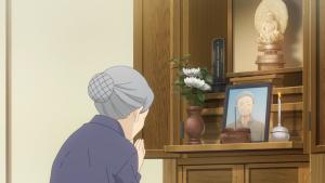 A avó da Yuu reza no santuário do avô